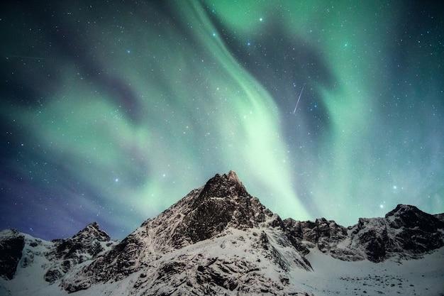노를 랜드의 별똥별과 함께 춤을 추는 북극광이있는 눈 덮인 산 프리미엄 사진