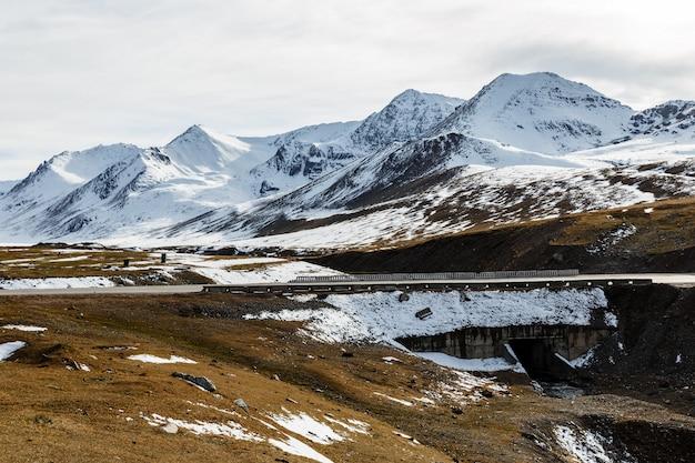 アラベル峠の雪に覆われた山の頂上、キルギスタンのビシュケクオシュ高速道路m41の橋 Premium写真