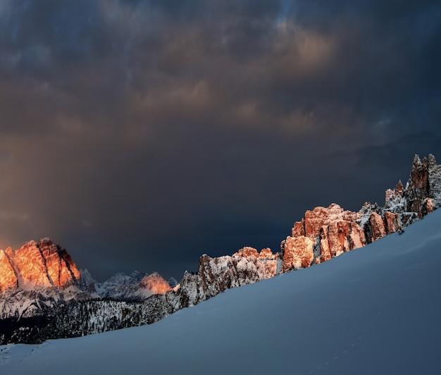 Rocce innevate a dolomiten, le alpi italiane sotto il cielo nuvoloso scuro Foto Gratuite