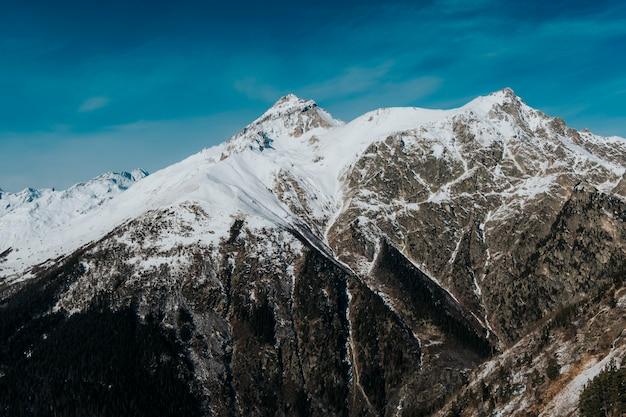 화창한 날씨에 산의 눈 덮인 바위 봉우리. Dombai 산을 닫습니다. 프리미엄 사진