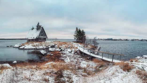 러시아 마을 Rabocheostrovsk의 해안에 정통 집 눈 덮인 겨울 풍경. 파노라마 뷰. 프리미엄 사진
