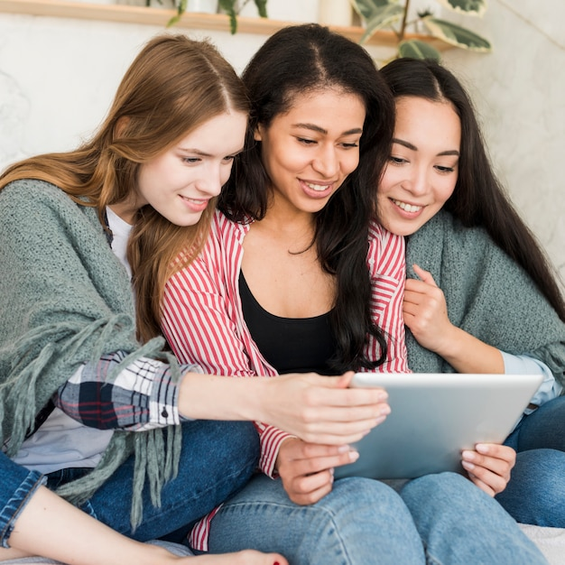Snugging under blanket girls sitting and looking at tablet screen Free Photo