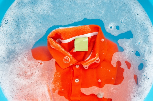 Soak a cloth before washing, orange polo shirt. top view Premium Photo
