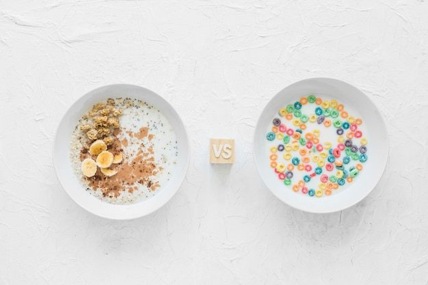 Soaked oatmeal versus cereals on white bowl over textured backdrop Free Photo