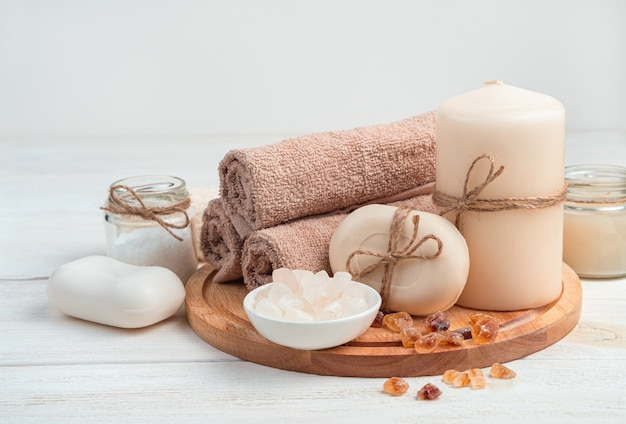 Soap, candles, towel and salt on a board on a white wooden background. the side view is horizontal. the concept of spa treatments. Premium Photo