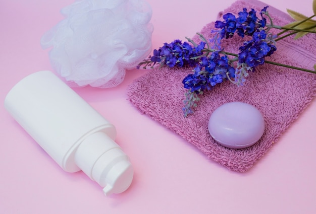 Soap; towel; lavender flower; loofah and cosmetic bottle on pink backdrop Free Photo