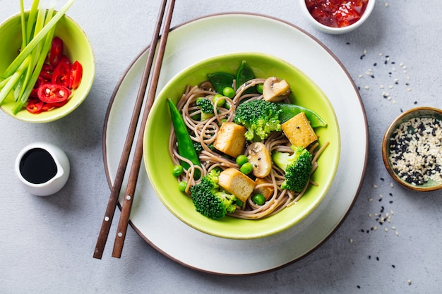 Soba noodles with vegetables and fried tofu in a bowl. top view. close up. Premium Photo