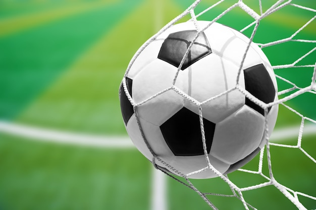 Soccer ball in goal net with soccer field background Premium Photo