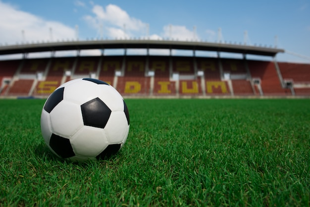 Soccer ball on grass with stadium background Free Photo