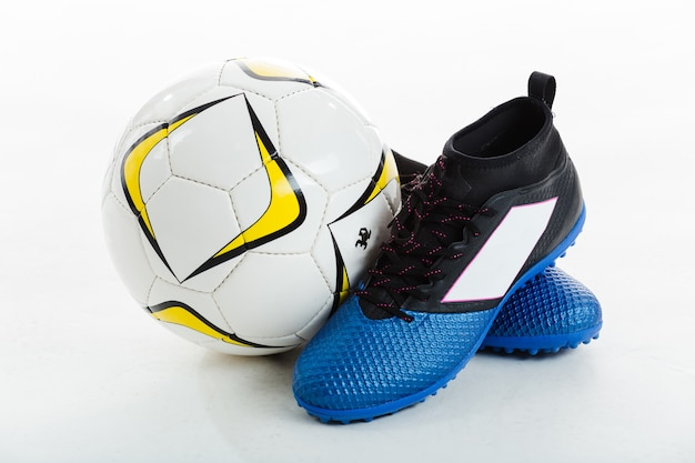 Soccer ball next to cleats Free Photo
