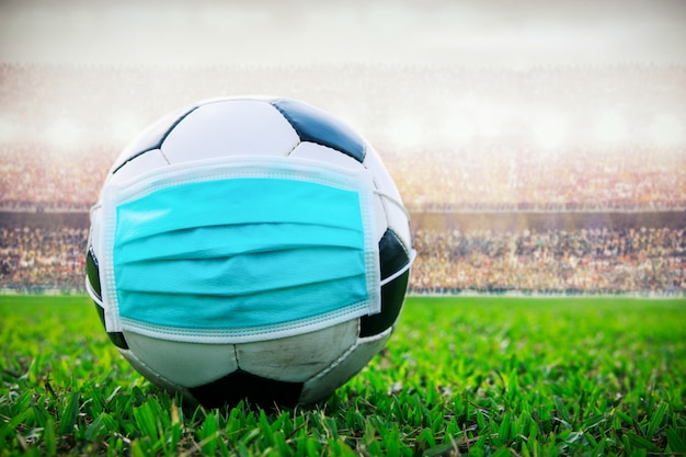 Soccer ball with medical mask in the stadium. all event of soccer pause break. covid-19 spreading outbreak Premium Photo
