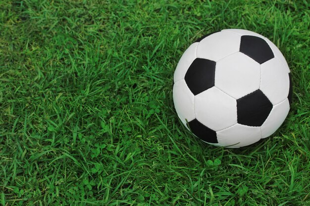Soccer black and white ball on the green grass, top view. empty space for text on the left. Premium Photo