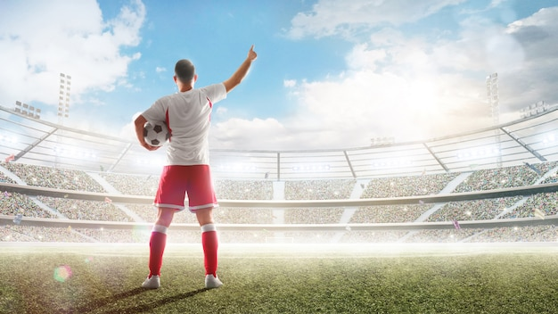 Soccer concept. soccer player holds a soccer ball on the professional stadium and talking to fans. Premium Photo