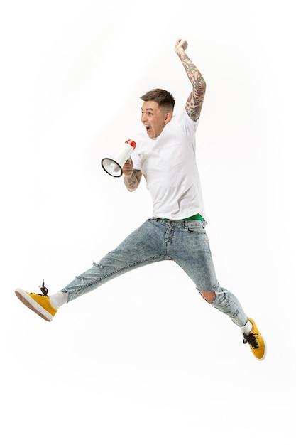Футбольный фанат прыгает на белом фоне. молодой человек как футбольный болельщик с мегафоном, изолированным на оранжевой студии. Бесплатные Фотографии