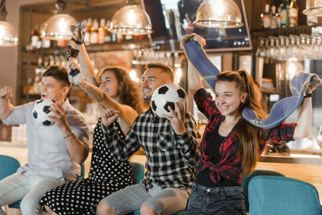 Soccer fans sitting in bar celebrating victory Free Photo