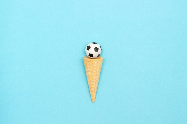 Soccer or football ball in ice cream waffle cone. concept sports entertainment. Premium Photo