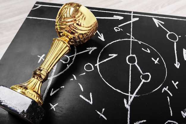 Soccer plan chalk board with formation tactic and trophy Premium Photo