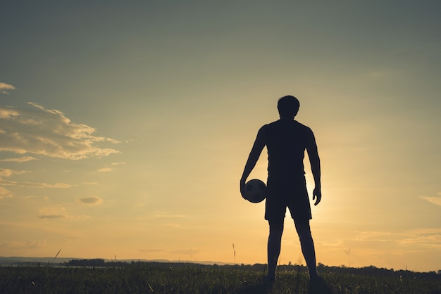 Soccer player man standing rear view in silhouette isolated on sunset background Premium Photo