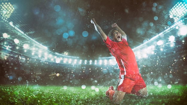 Soccer striker in red uniform rejoices for the victory at the stadium Premium Photo