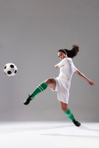 Soccer woman kicking football Free Photo