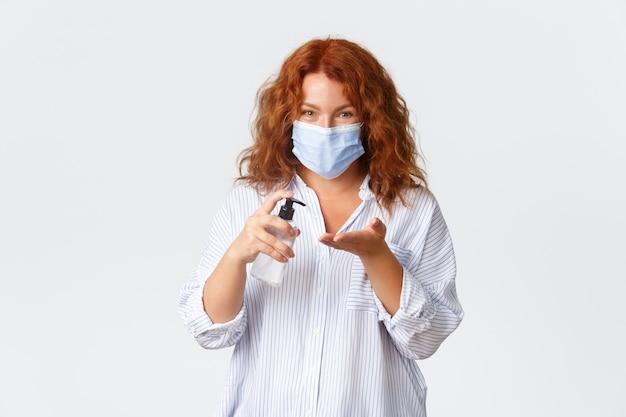 Социальное дистанцирование, меры профилактики коронавируса и концепция людей. симпатичная рыжая женщина средних лет наносит дезинфицирующее средство для рук на руки и носит медицинскую маску, безопасность прежде всего. Premium Фотографии