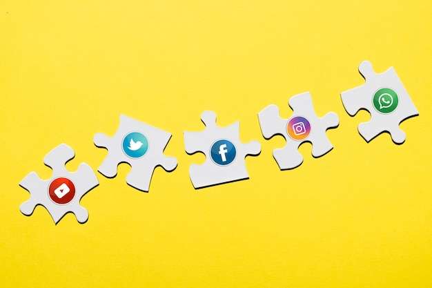 Social media icon on white puzzle piece over yellow backdrop Free Photo