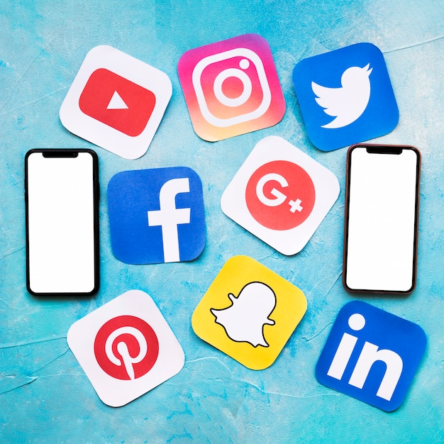 Значки социальных сетей с двумя пустыми сотовый телефон на синей окрашенной стене Бесплатные Фотографии