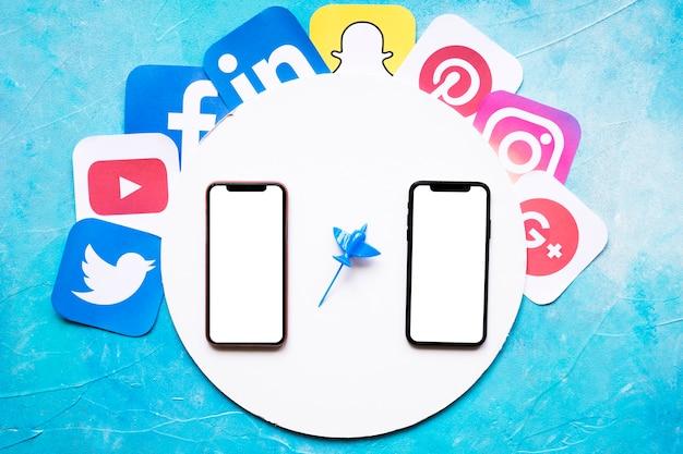Значки социальных мобильных приложений вокруг круглой белой рамки с двумя мобильными телефонами на синем фоне Бесплатные Фотографии
