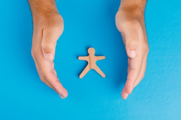 Social protection concept on blue table flat lay. hands taking care of wooden human figure. Free Photo