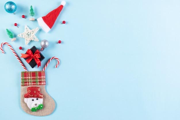 Носок и рождественские украшения на пастельно-синем фоне. красивая рождественская открытка с копией пространства. Premium Фотографии