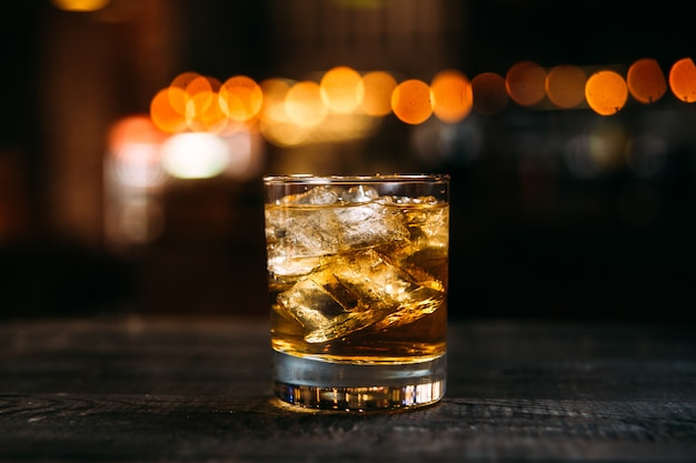 Soda whiskey cocktail with ice cubes in the old fashion glass on the wooden table with blurry bokeh lights background Premium Photo