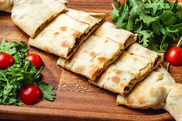 Соде вид сырного пиджа с мясом, луком, помидорами черри и рукколой на подносе Бесплатные Фотографии