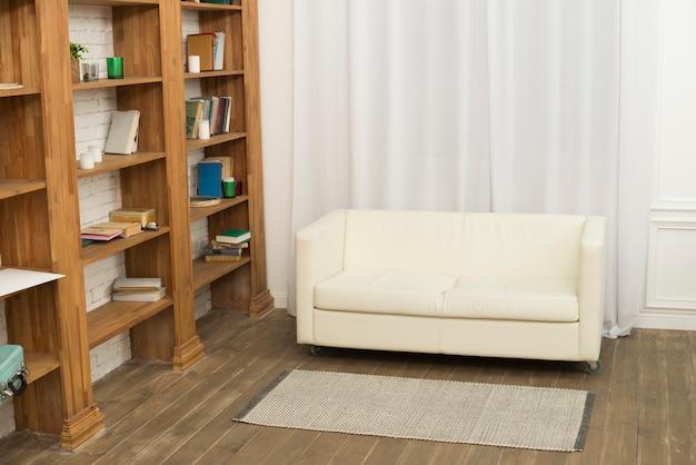 Sofa near bookshelves in room Free Photo