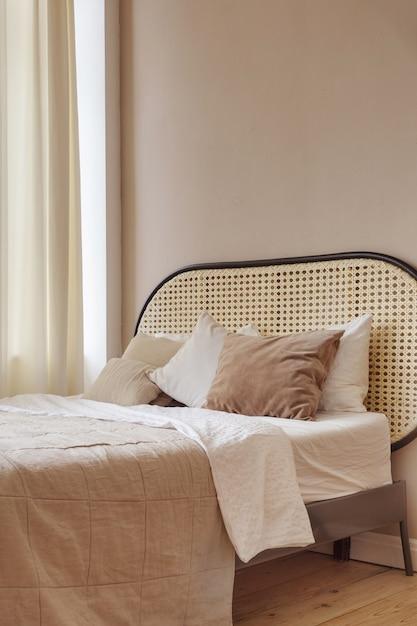 Мягкая кровать с подушками и одеялом расположена в уютной спальне в современной квартире Premium Фотографии