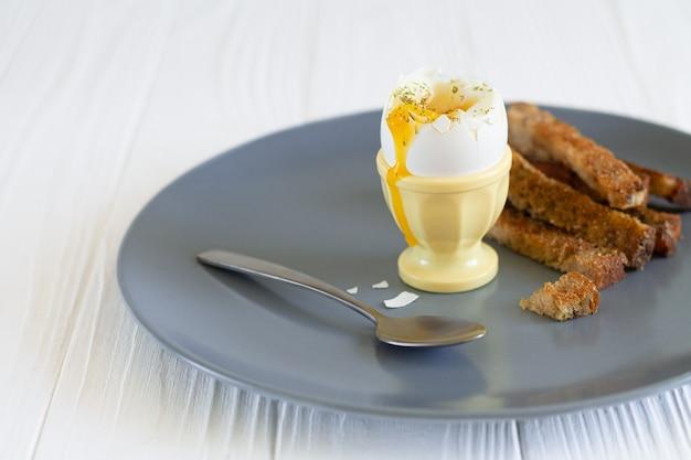 朝食にトーストしたパンを入れた卵カップの半熟半熟卵 Premium写真