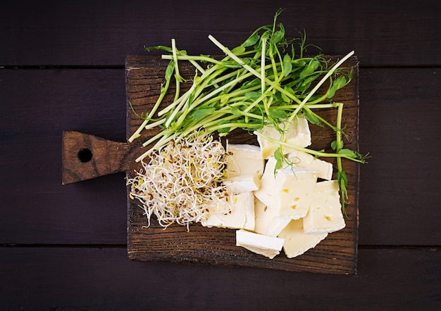 Soft brie cheese and microgreens on wooden board Premium Photo
