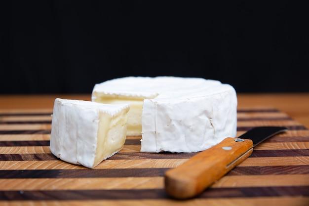 Мягкий сыр и нож лежал на деревянной доске Бесплатные Фотографии