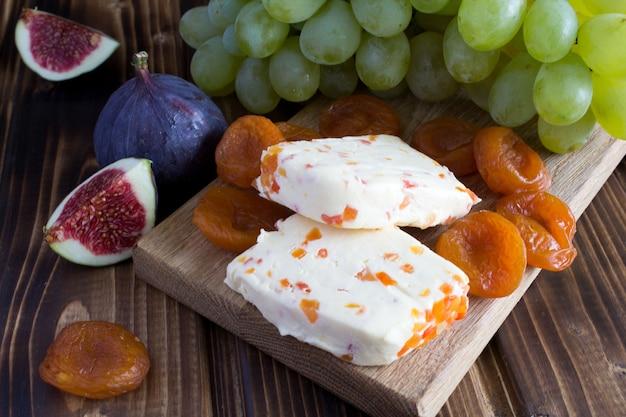 木製のまな板にドライアプリコットとフルーツのソフトチーズ Premium写真