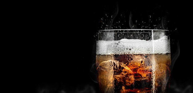 Soft drink glass with ice splash on cool smoke Premium Photo