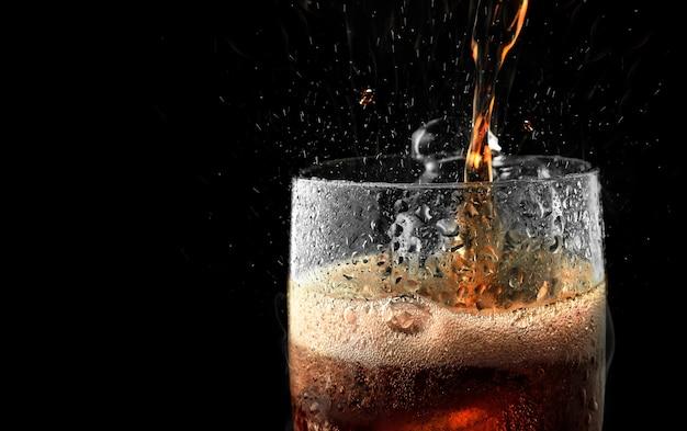 Soft drink glass with ice splash on dark background. Premium Photo