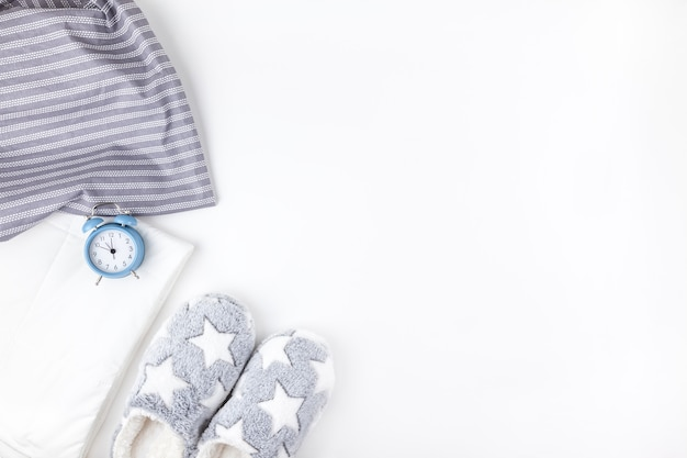 Soft fluffy slippers and blue alarm clock Premium Photo