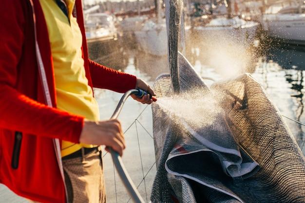 Мягкий фокус капель воды, выходящих из шланга, моряк или капитан, владелец яхты смывает соленые остатки с паруса, грота или спинакера, когда парусная лодка пришвартована во дворе или в гавани Бесплатные Фотографии
