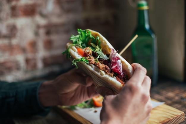 クールなレストランやカフェでおいしい朝食を食べている男性のソフトフォーカスショット、ライ麦パンのトーストの上にワカモレやアボカドを塗る 無料写真
