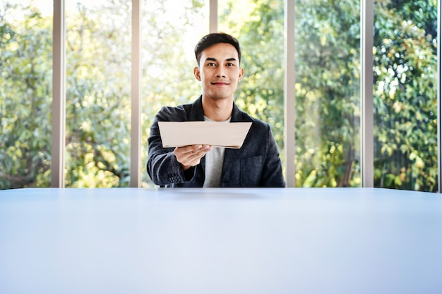 Soft focus of young businessman sitting at the table in office by glass window Premium Photo