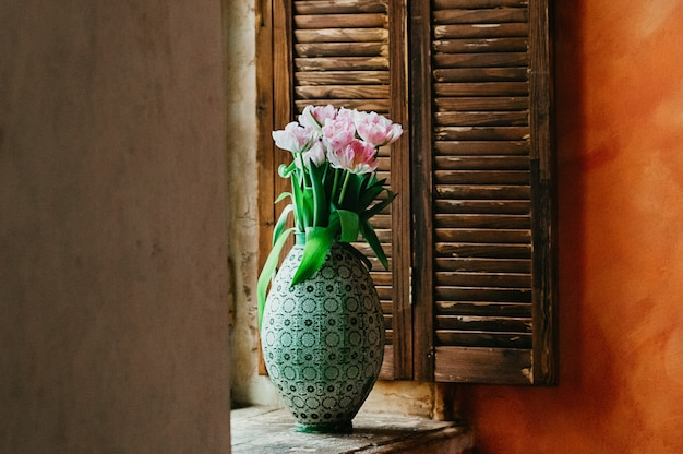 A soft focused bouquet of flowers in a vase on a window sill Premium Photo