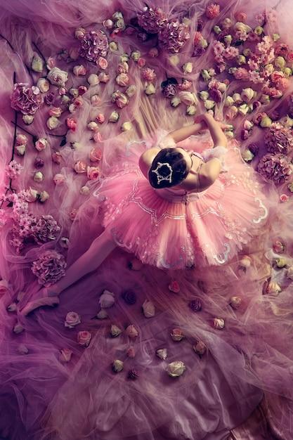 Morbido a casa. vista dall'alto di bella giovane donna in tutu di balletto rosa circondato da fiori. atmosfera primaverile e tenerezza nella luce del corallo. concetto di primavera, fioritura e risveglio della natura. Foto Gratuite