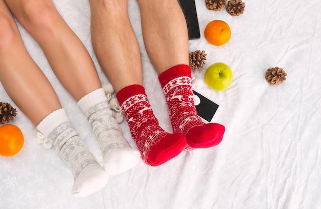 電話と果物、トップの視点でベッドの上の女性と男性の柔らかい写真。暖かいウールの靴下でカップルの女性と男性の足。 無料写真