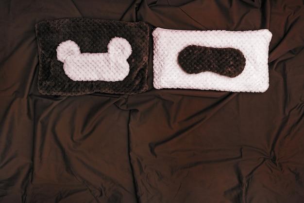 Soft pillow and sleep mask on dark crumpled sheet. Premium Photo