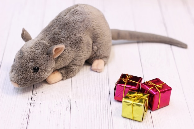Мягкая игрушка серая крыса возле новогодних украшений в виде подарков Premium Фотографии