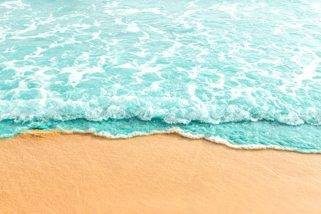 Soft wave of turquoise ocean on sandy beach Free Photo